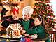 A grandmother and her granddaughter decorate a gingerbread house at Christmas.
